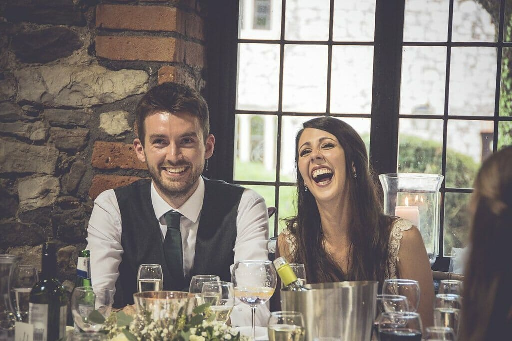Bride and Groom laughing mid speech at Pencoed House Cardiff
